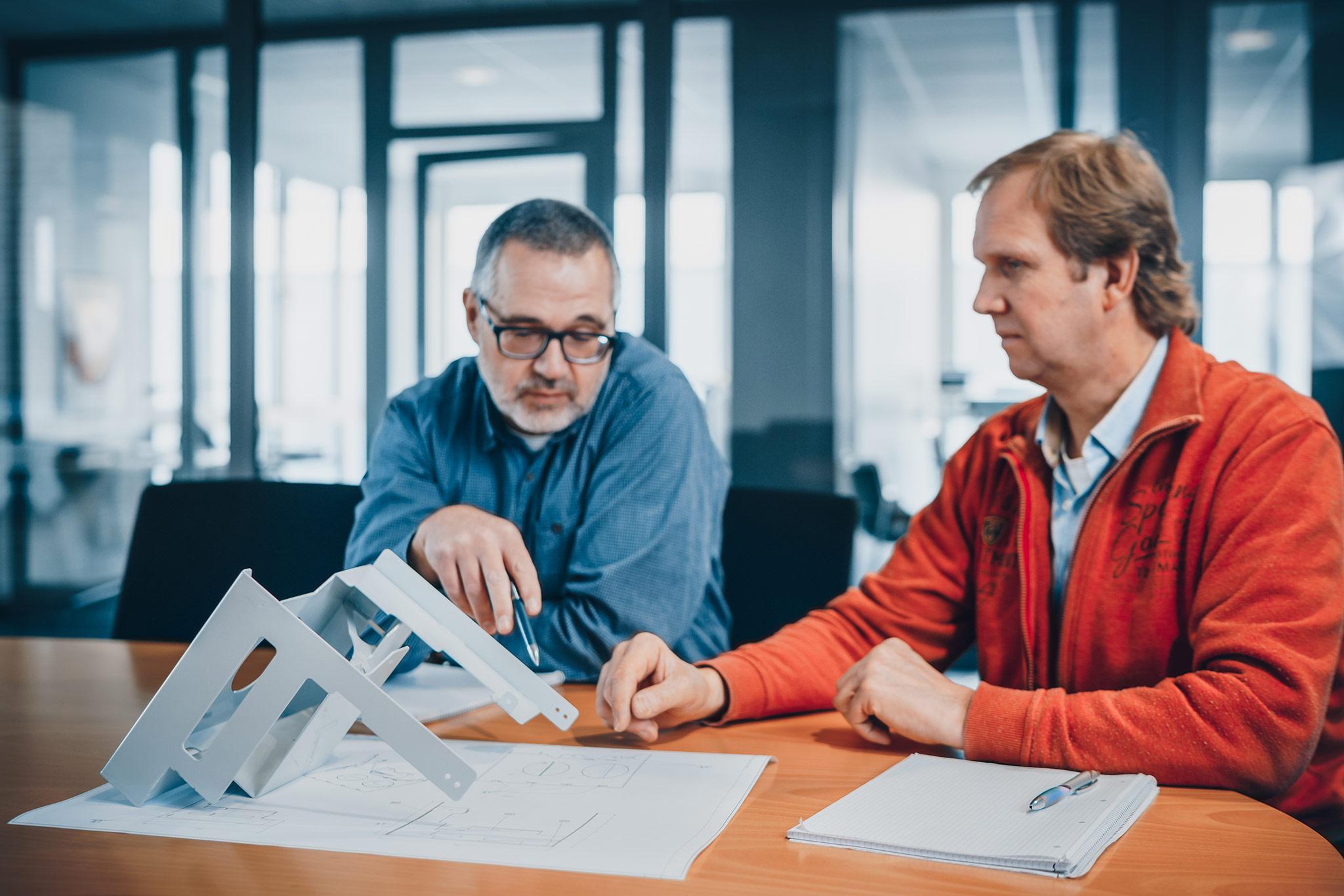 Techniker diskutieren am Tisch mit Bauteil